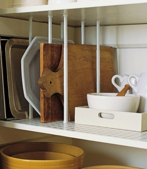 Storing baking sheets, cutting boards, and sturdy platters upright on kitchen shelves frees space and keeps you from having to lift a heavy stack.